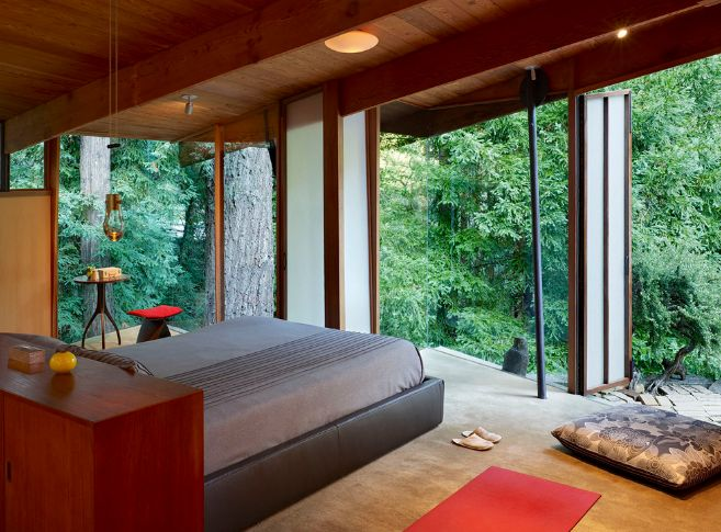 Stunning bedroom design with forest view through large windows
