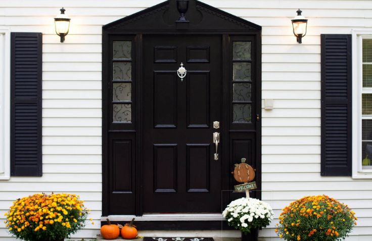White Exterior With Black Front House And Fall Poted Flowers