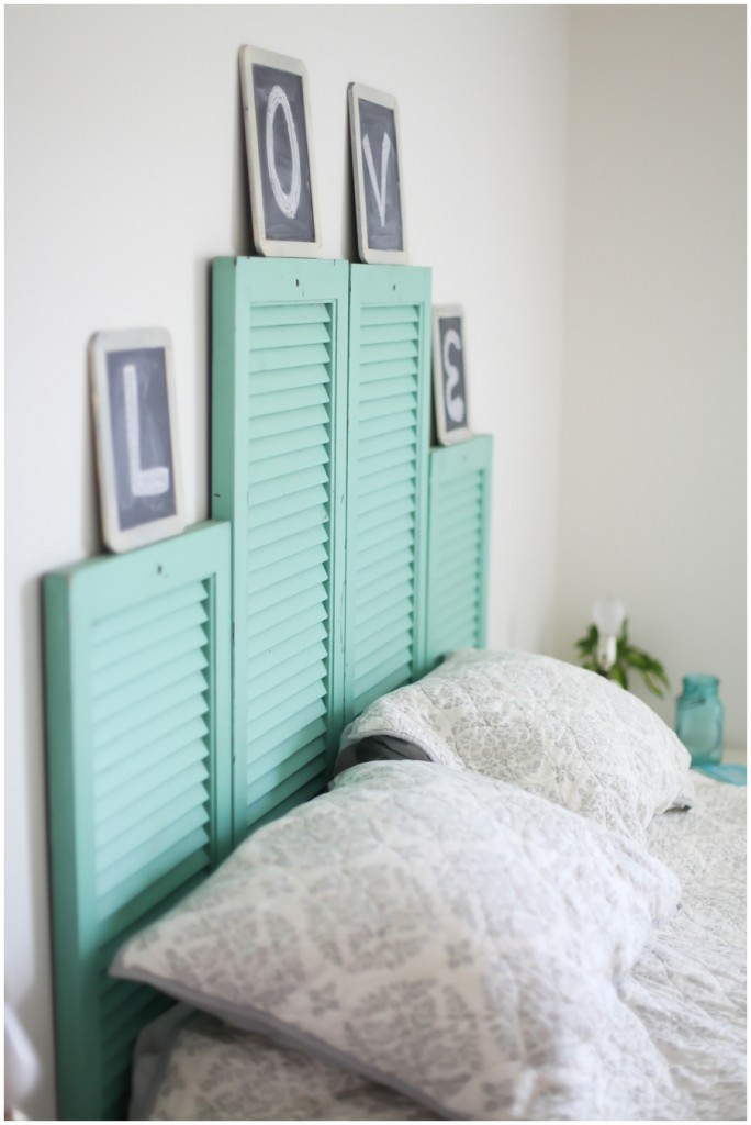 Old turquoise painted window shutters used like headboard