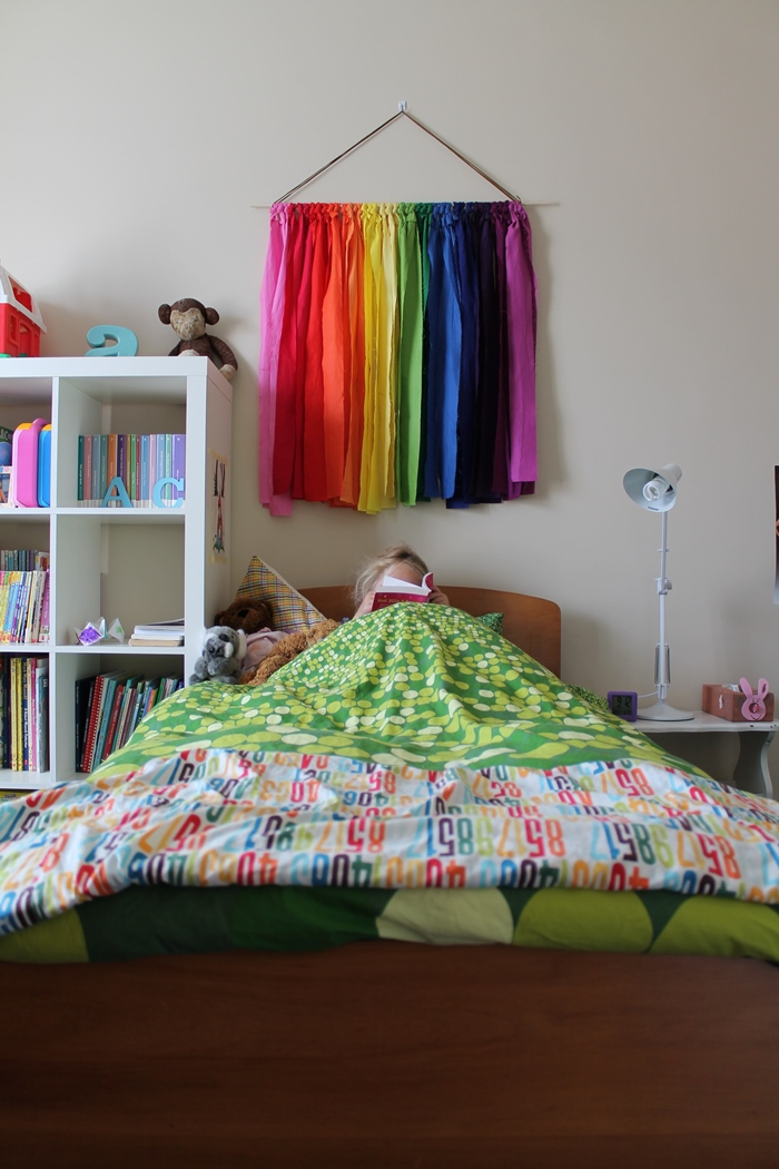 Rainbow wall hanging above bed