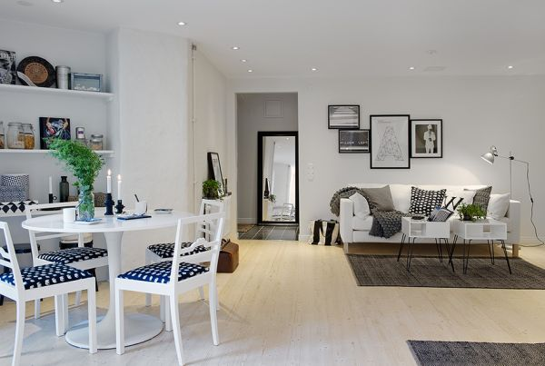 A small, white apartment with black accents and modern furniture