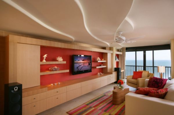Contemporary living room featuring a large wall unit with a red background