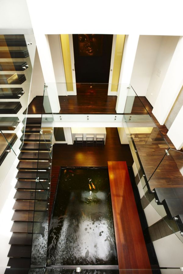 Renovated residence in singapore with a koi pond inside for Modern koi pond design photos