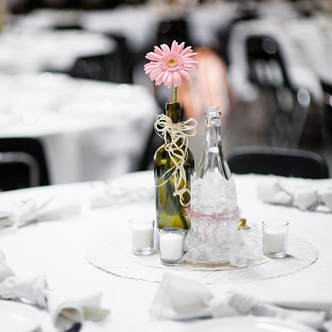 Empty glass bottles fill in as gorgeous wedding centerpieces for Using wine bottles as centerpieces for wedding