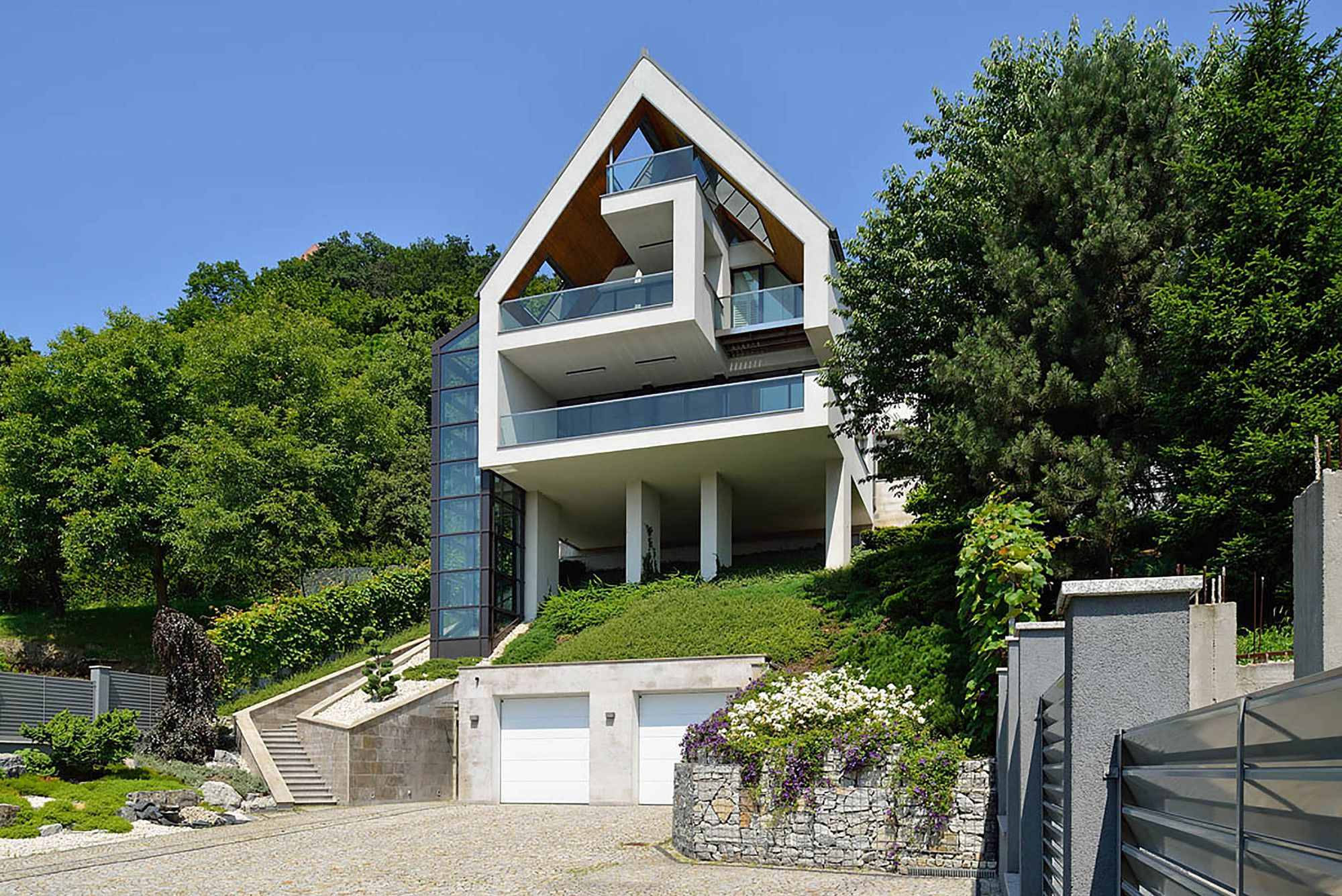 A house on a slope connects to its surroundings through a for Steep hillside house plans
