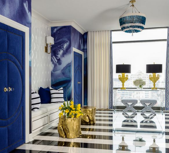 Blue decor hallway featuring gold stumps and beaded chandelier