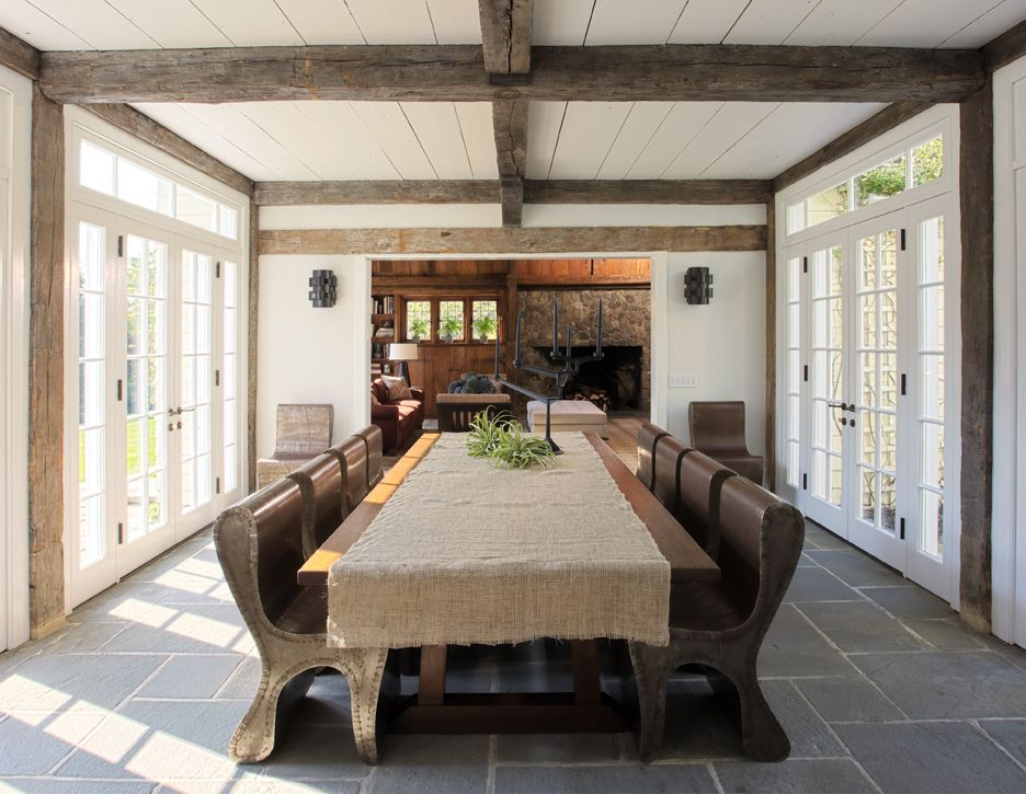 The home's dining room features an enormous table, paired with unusual chairs, reminiscent of church pews.