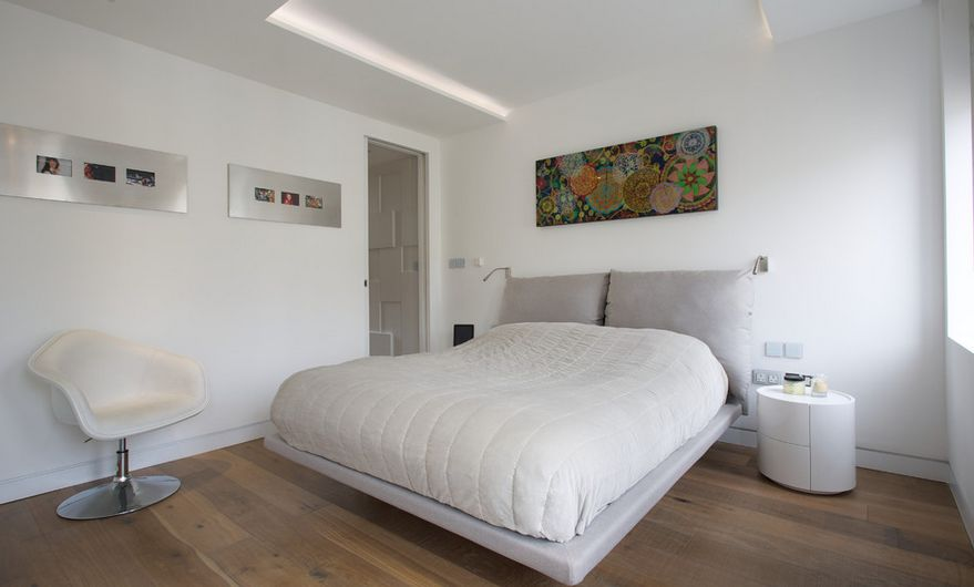 Hardwood bedroom floor with a grey bed