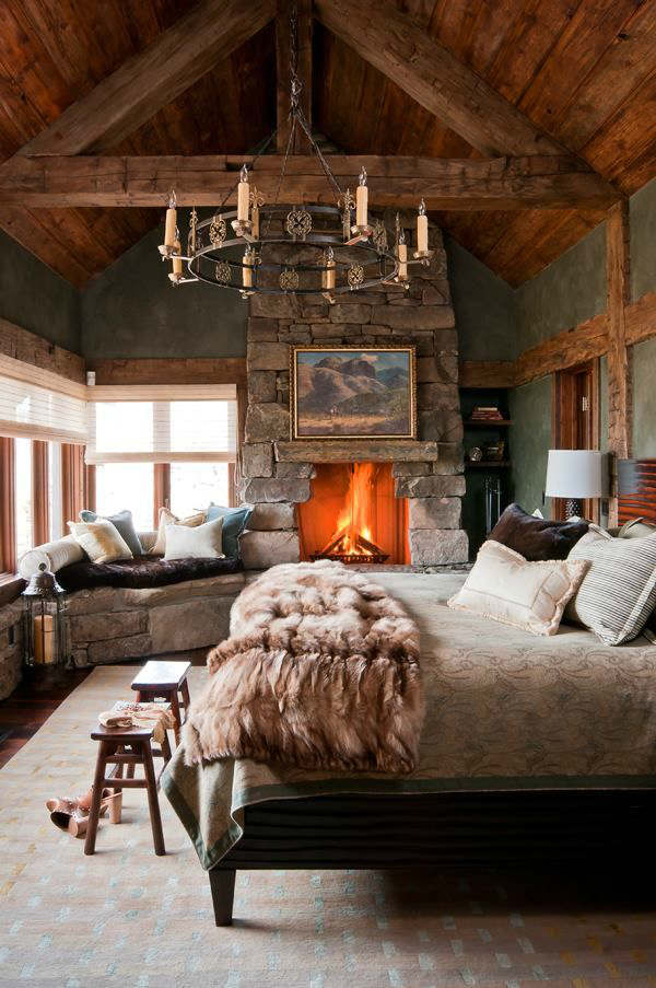 Master rustic bedroom design with chandelier and fireplace