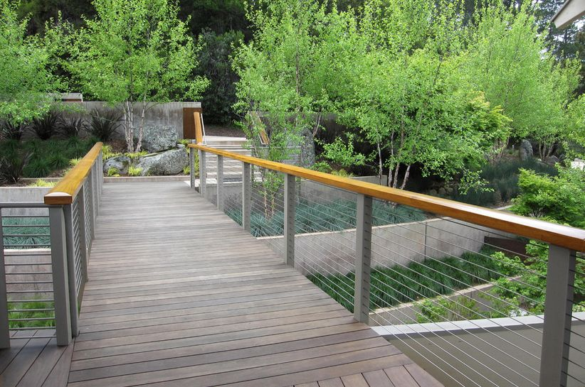 Modern backyard bridge with cable railings