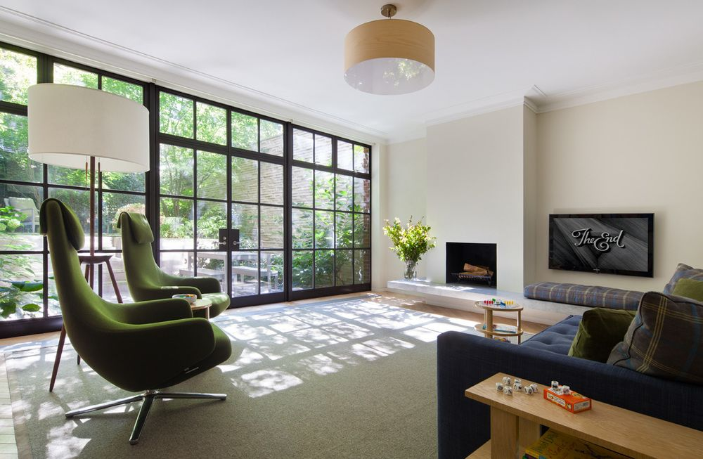 The green accent chairs in the family room seem to mimic the view outside on the patio.