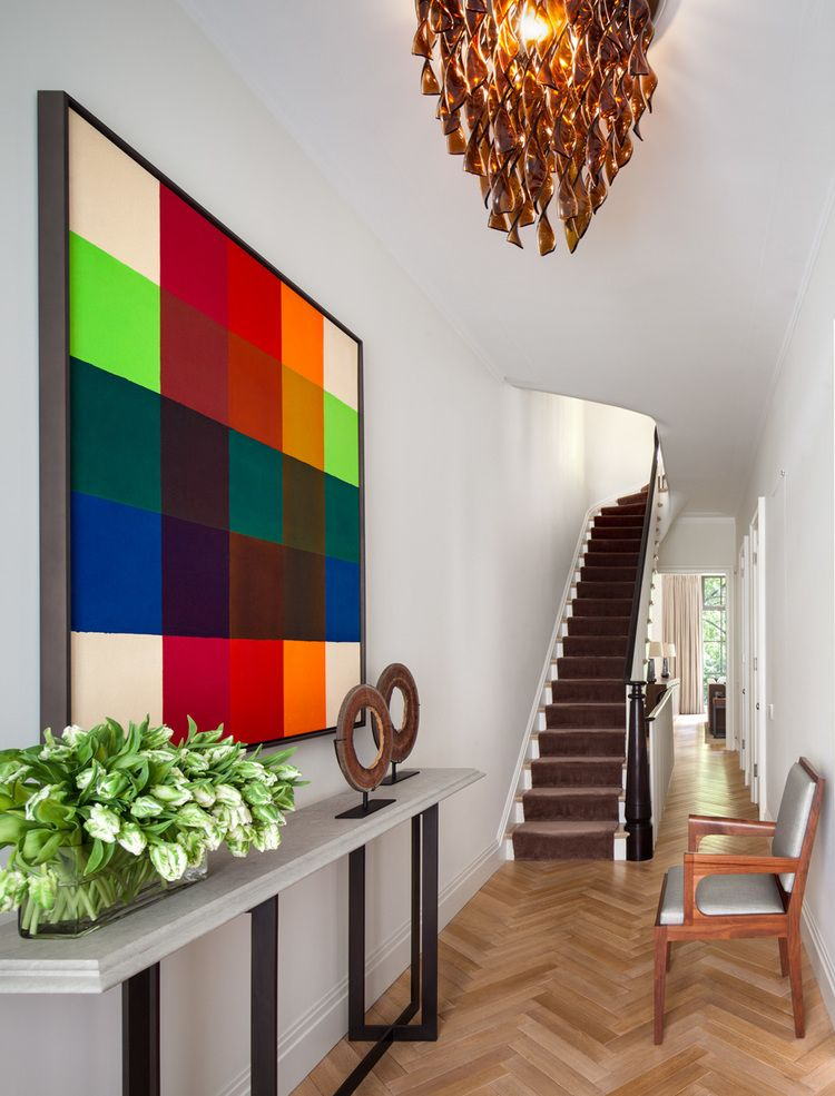 Modern art is a colorful pop in this sophisticated entryway.