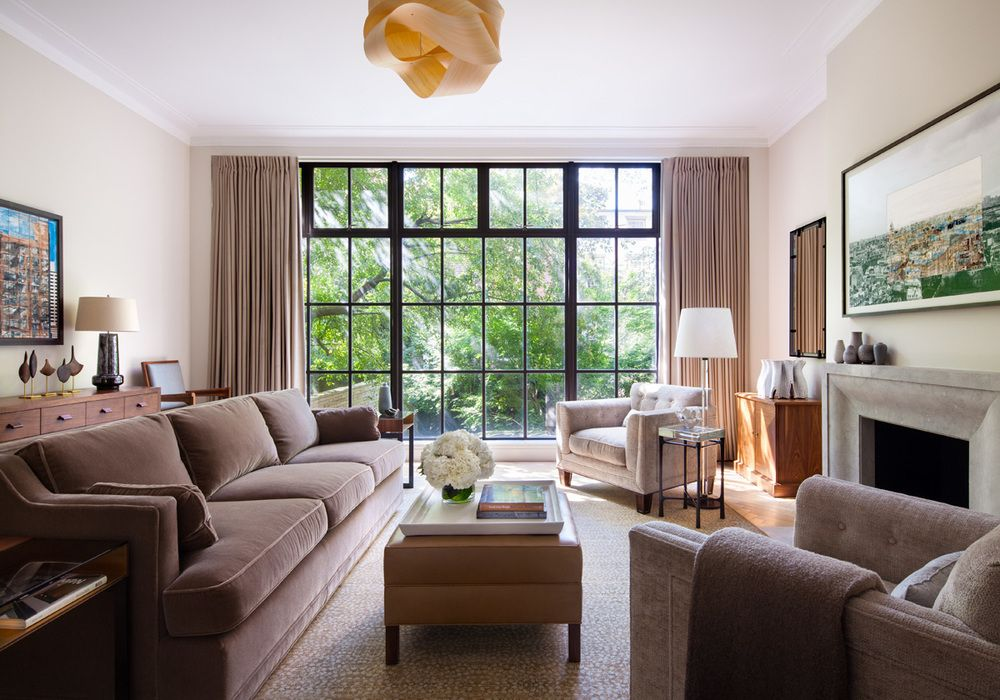 Floor to ceiling paned windows that offer a prized view of the nature outside are the focal point of this tranquil sitting room.