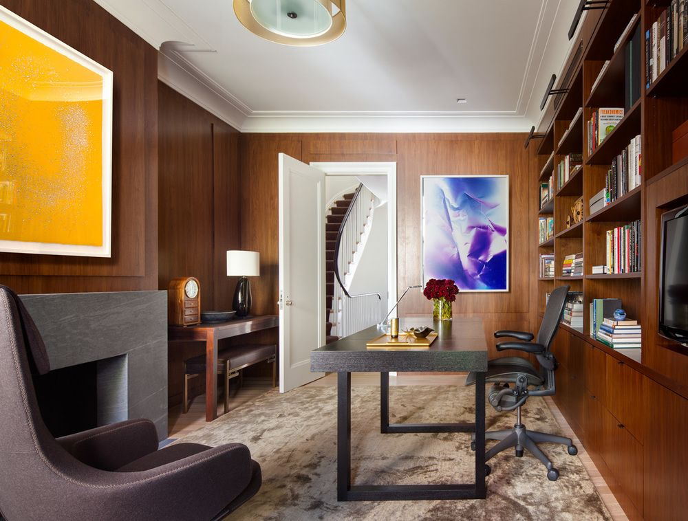 The wood walls makea serene backdrop for the homeowner's colorful artwork and the modern desk.