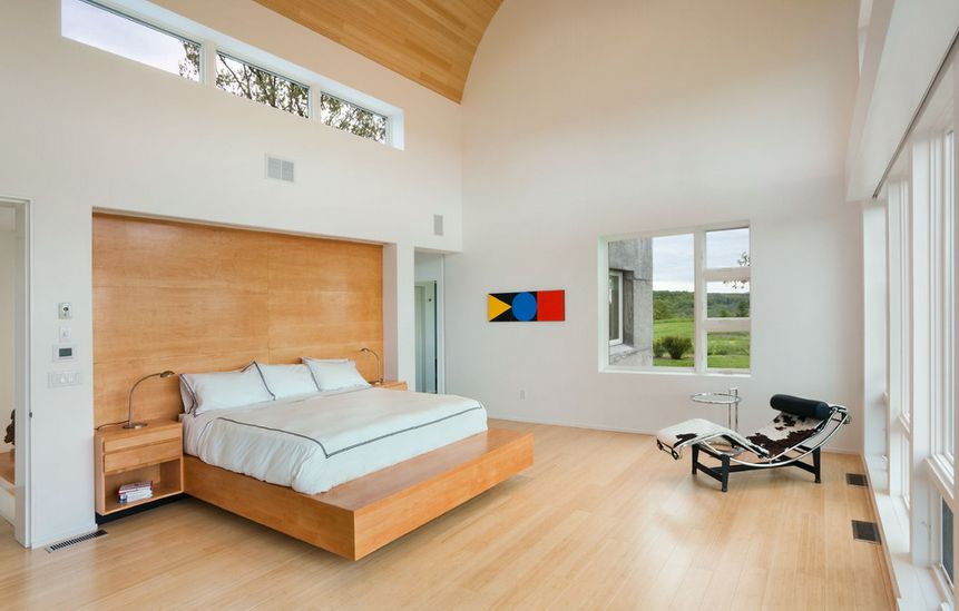 Wooden platform floating bed on a high ceiling bedroom