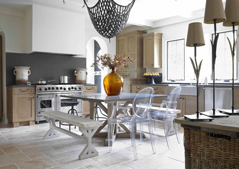 A bit of farmhouse and a bit of modern, this eclectic kitchen uses ghost chairs to tie the various dining elements together.