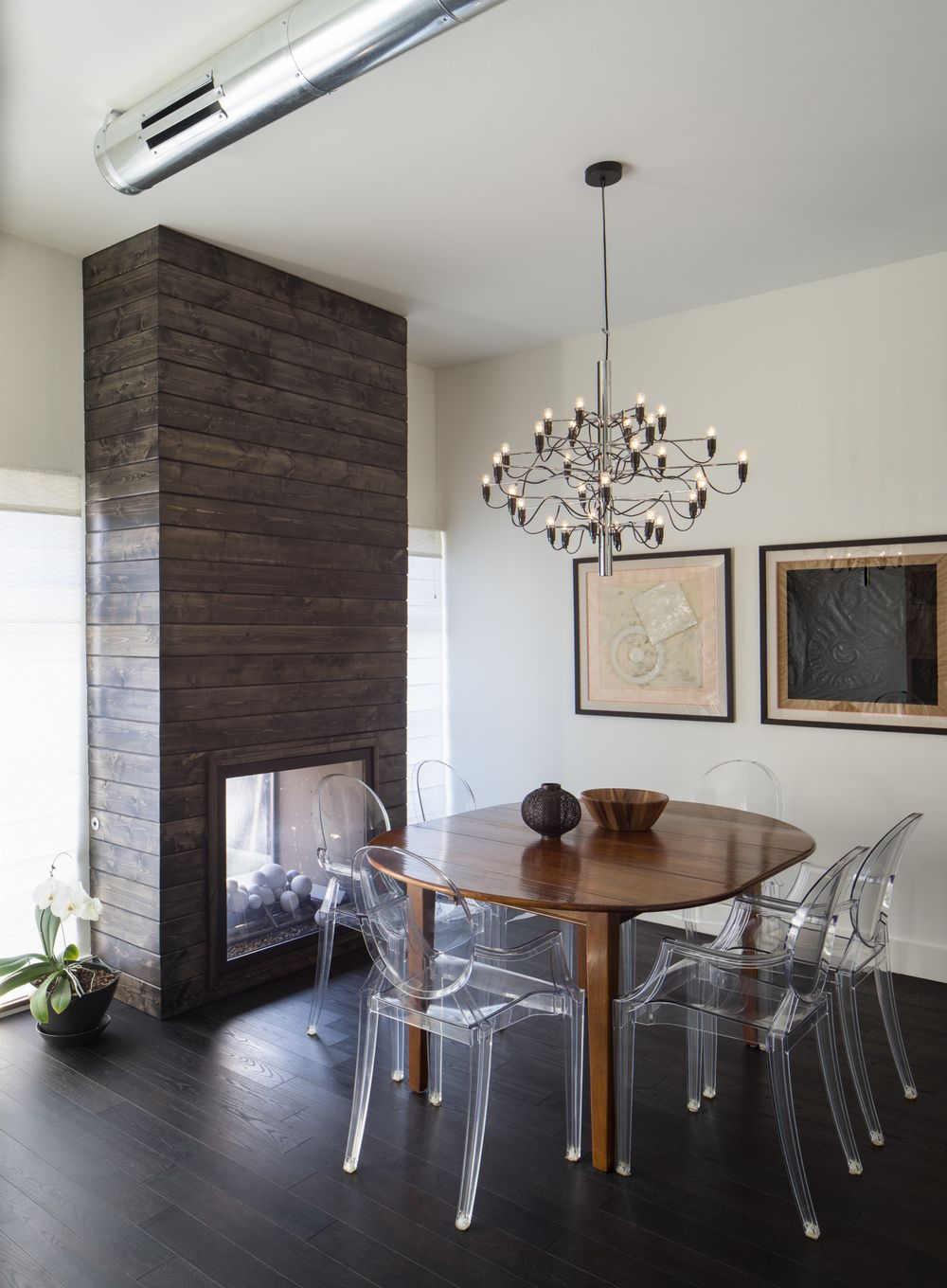 While wood is the major design element in this contemporary dining room, the Ghost chairs fit in, allowing the wood of the wall, fireplace and table to shine.