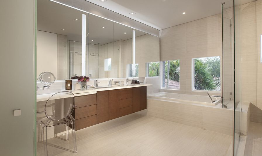 Mimicking the transparency of the glass shower, the ghost chair in this bathroom fits right in with the modern design.