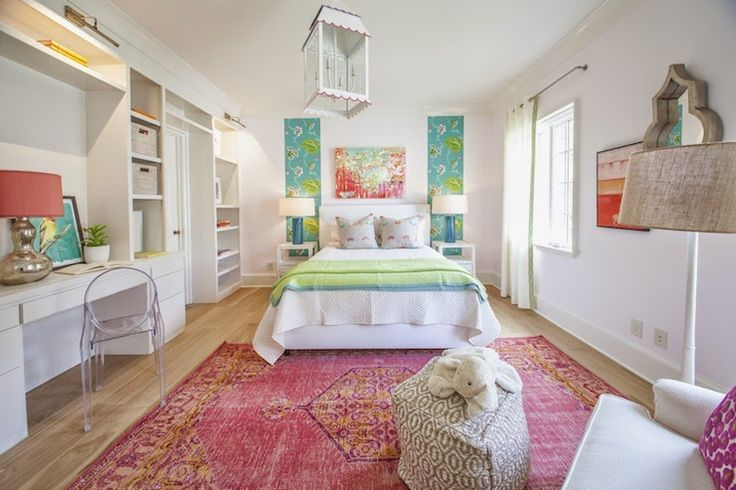 The lovely colored textiles and clean lines of the built-in shelving in this girl's bedroom remain the focus, thanks to the unobtrusive ghost chair.