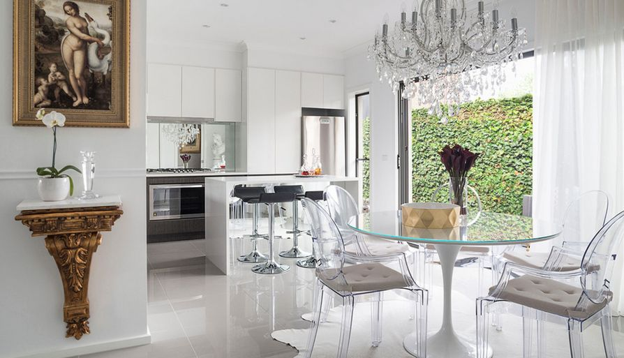 Glamorous and elegant, this kitchen and dining area is highlighted by the Ghost chairs, which have been enhanced with neutral chair pads.