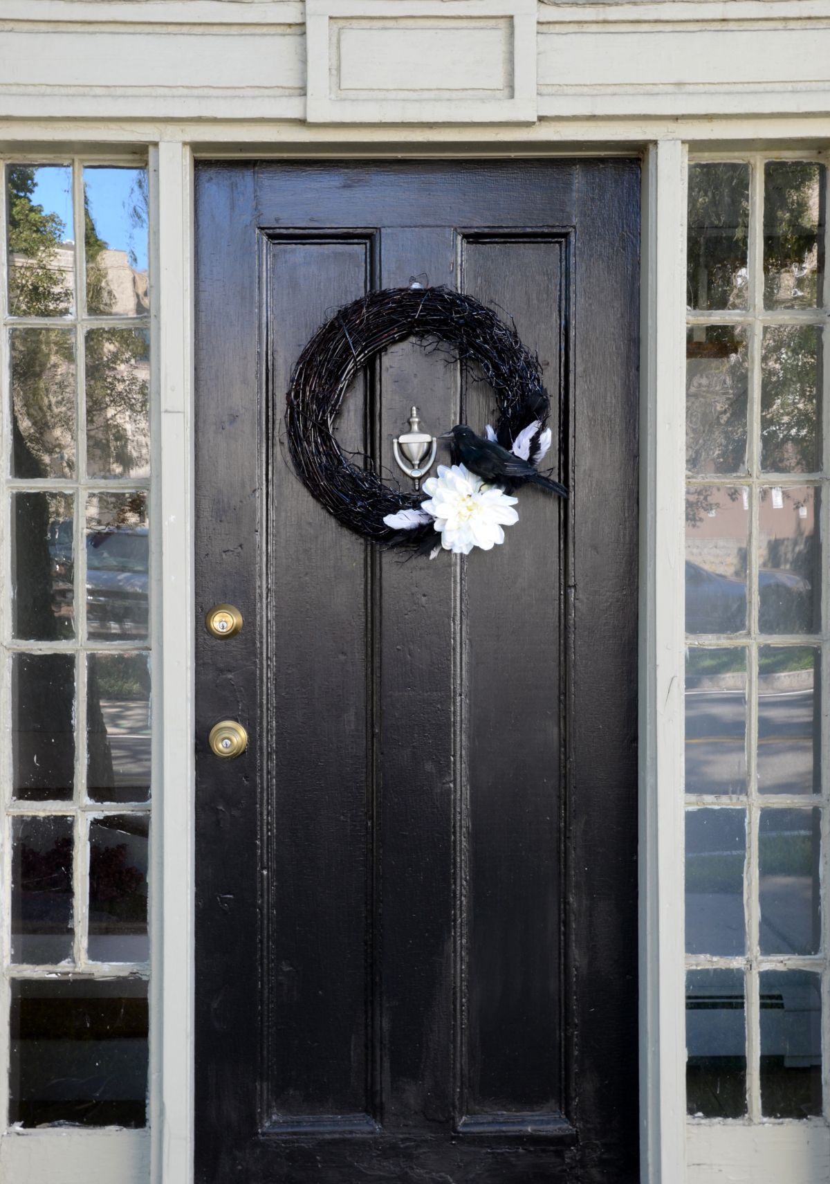 Black front door with a Halloween wreath