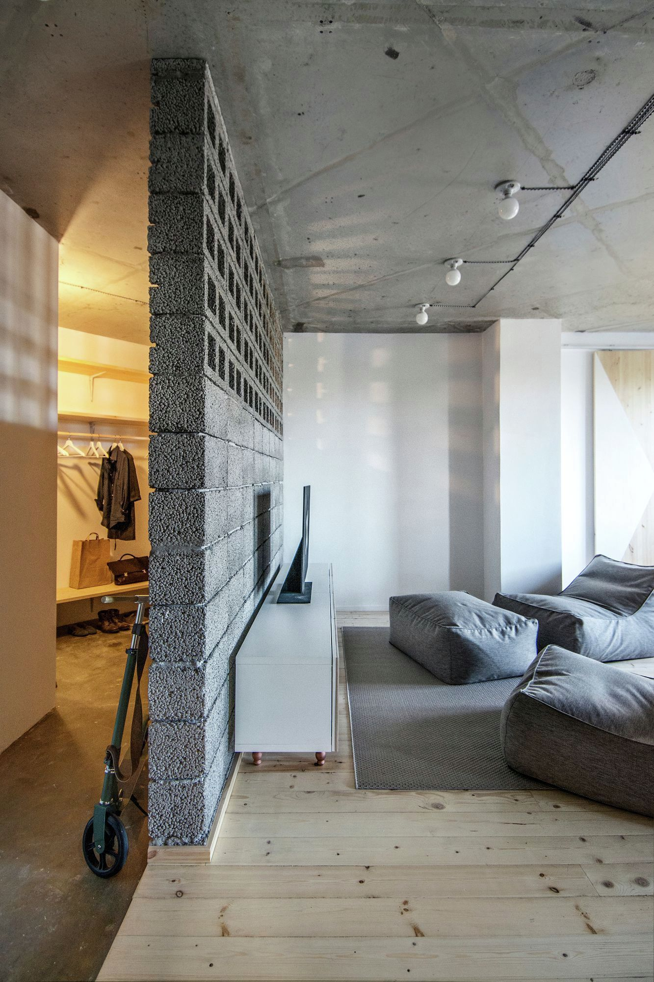 Eclectic apartment in St. Petersburg concrete wall divider and hallway