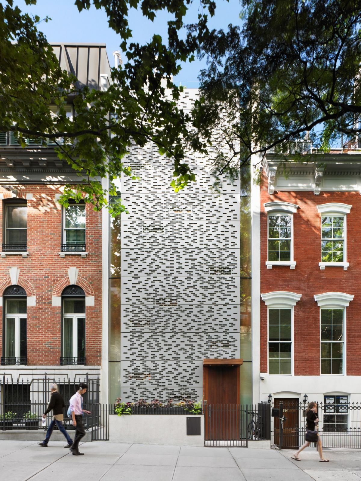 Perforated building facades that redefine traditional design for Nyc townhouse with garage