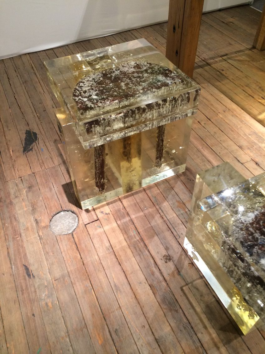 Inside the resin of the square bench, you can see one side of a round stool.