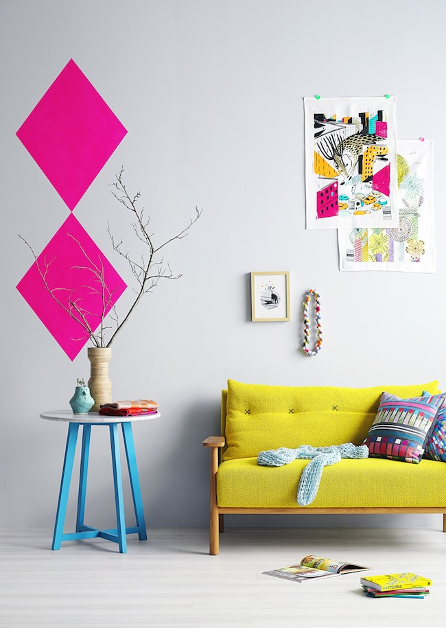 Bright yellow couch and a geometric pink wall decor
