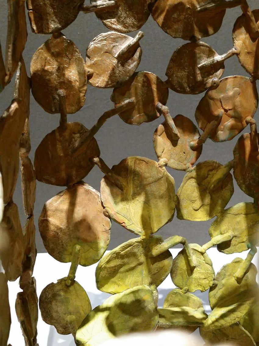 Each piece has a different color gradation, and with the varying light from different angles, reminds the viewer of dappled sunlight on the leaves.