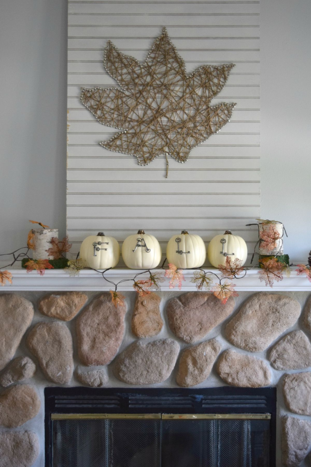 Rocks fireplace with pumpkins on mantel