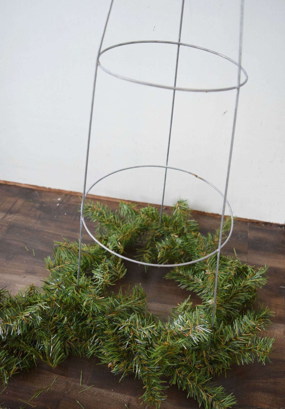 Adding garland to tomatoe cage
