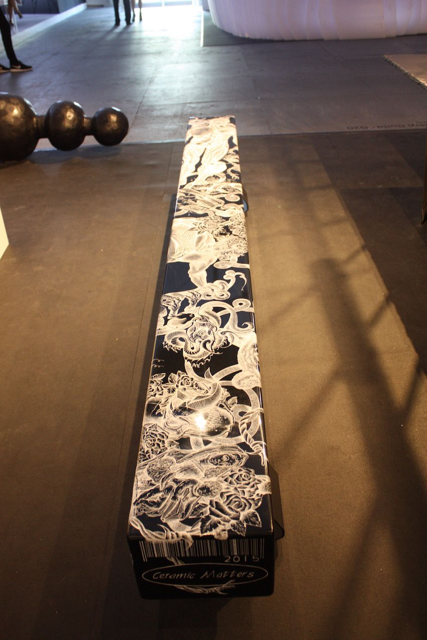 Long and lean, the bench features intricate tattoo-style designs.