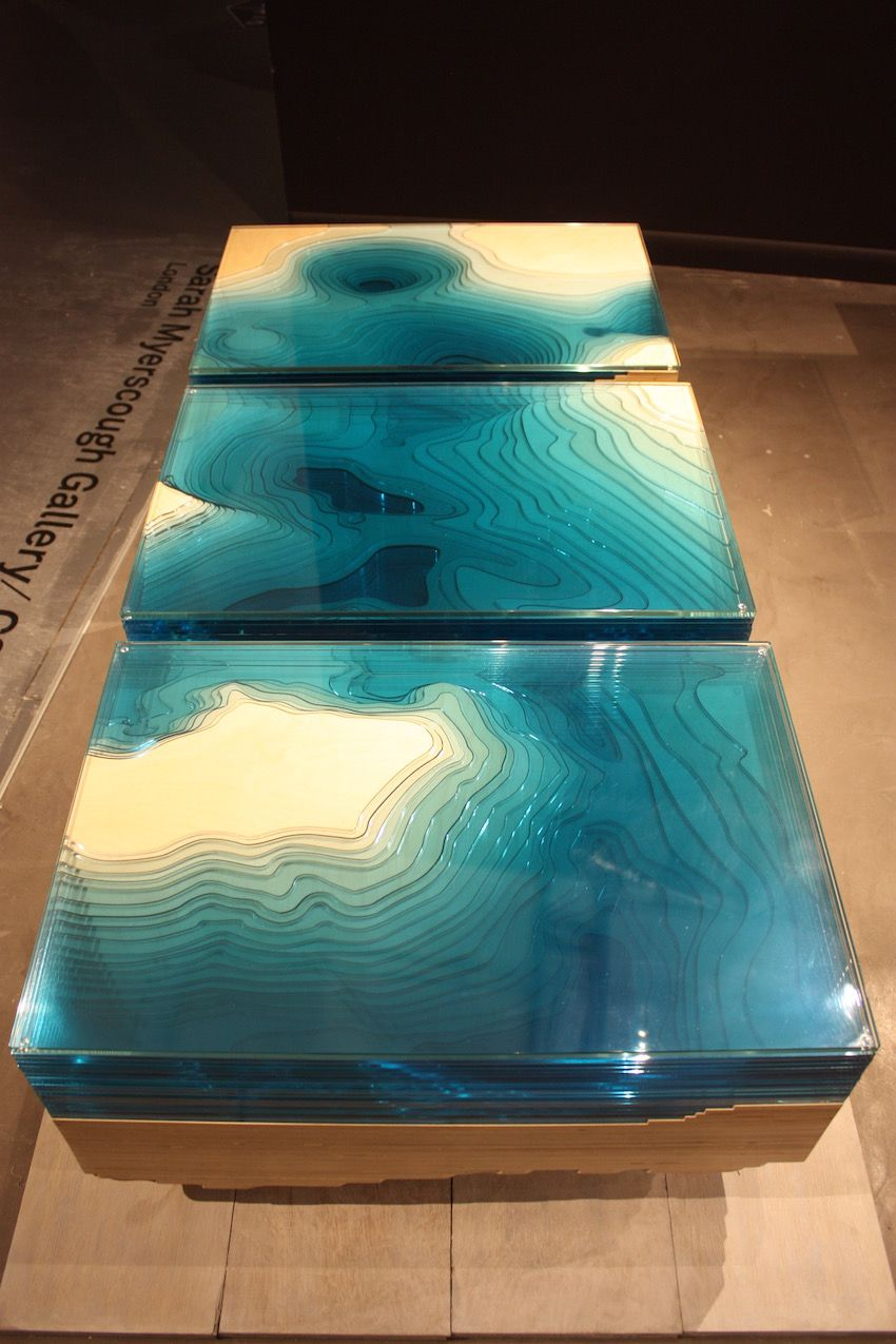 "According to the Mysercough website, the design team spent a year developing the table in their London studio. ""They experimented with sculpted glass, Perspex and wood, arranged like a 3-D representation of a geological map, manipulating perceptions of depth. The final product reflects more than something of the mesmeric abyss that had first captured Duffy's imagination."""