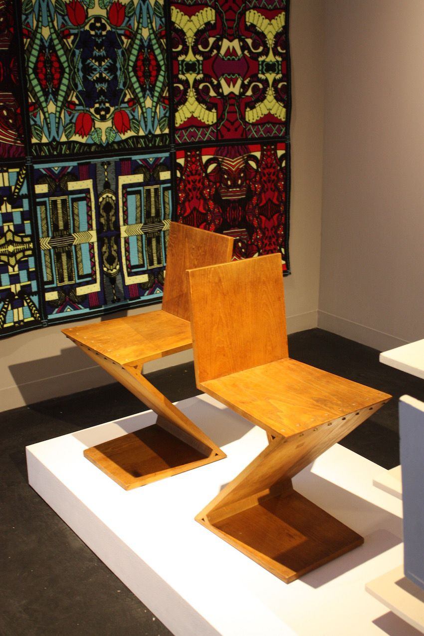 Made of red-stained elm, the chairs are secured with brass screws. Rietveld was a Dutch furniture designer and architect who was one of the principal members of the Dutch artistic movement called De Stijl.