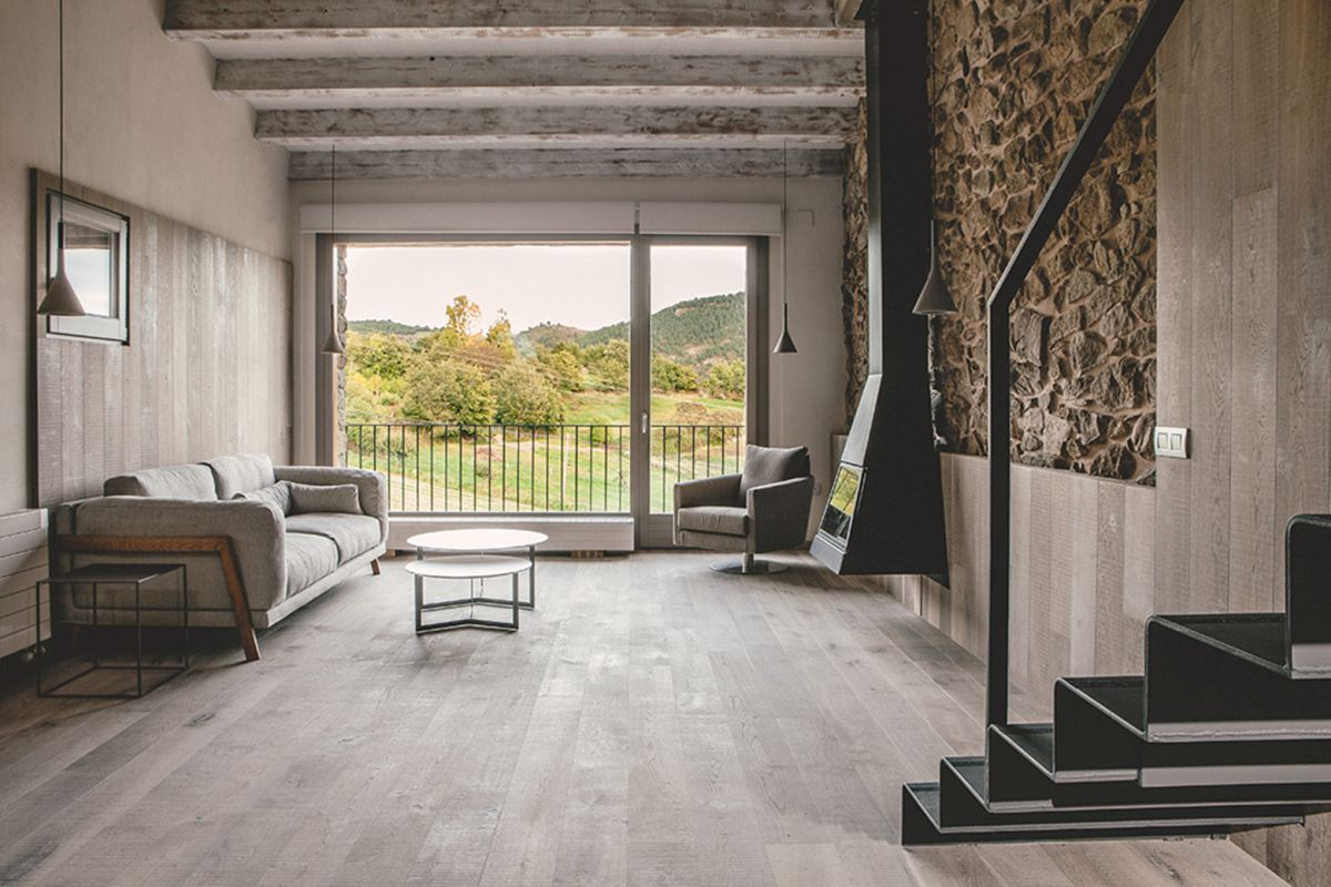 Rustic house gets rehabilitated in Spain - living room stone wall