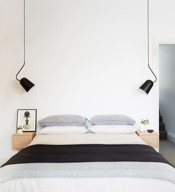 Bedroom with white walls and black pendant lamps