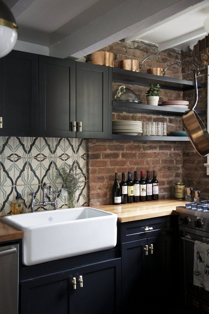 Black Farmhouse Kitchen With Exposed Brick Backsplash