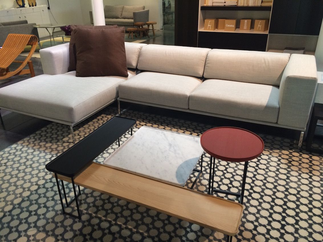 A mid-century modern style sectional and a stylish grouping of small tables could serve a drawing room or a family room, depending upon the accessories and other furnishings in the space.