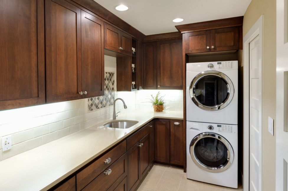 Small laundry room in darkwood and stacked washer