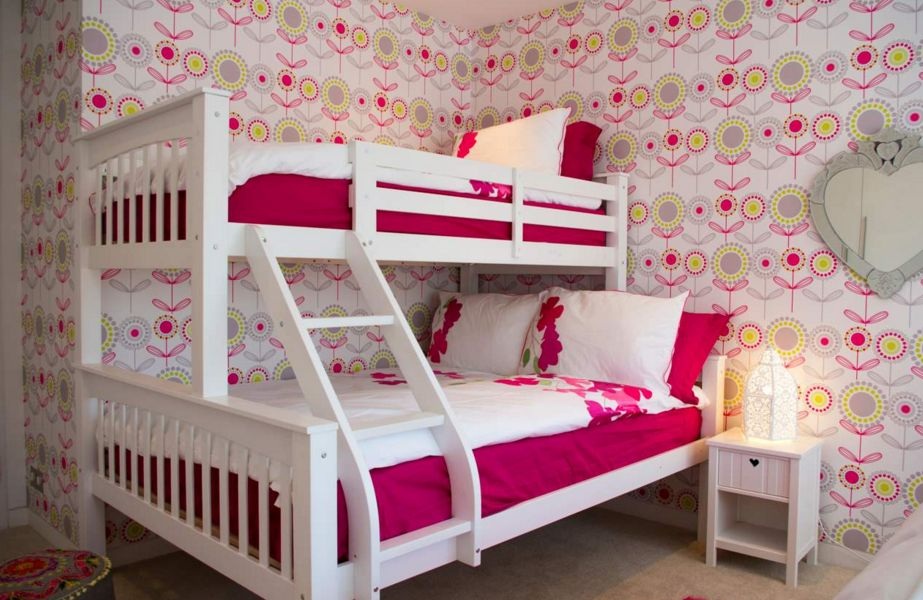kids room with pink wallpaper and bunk beds