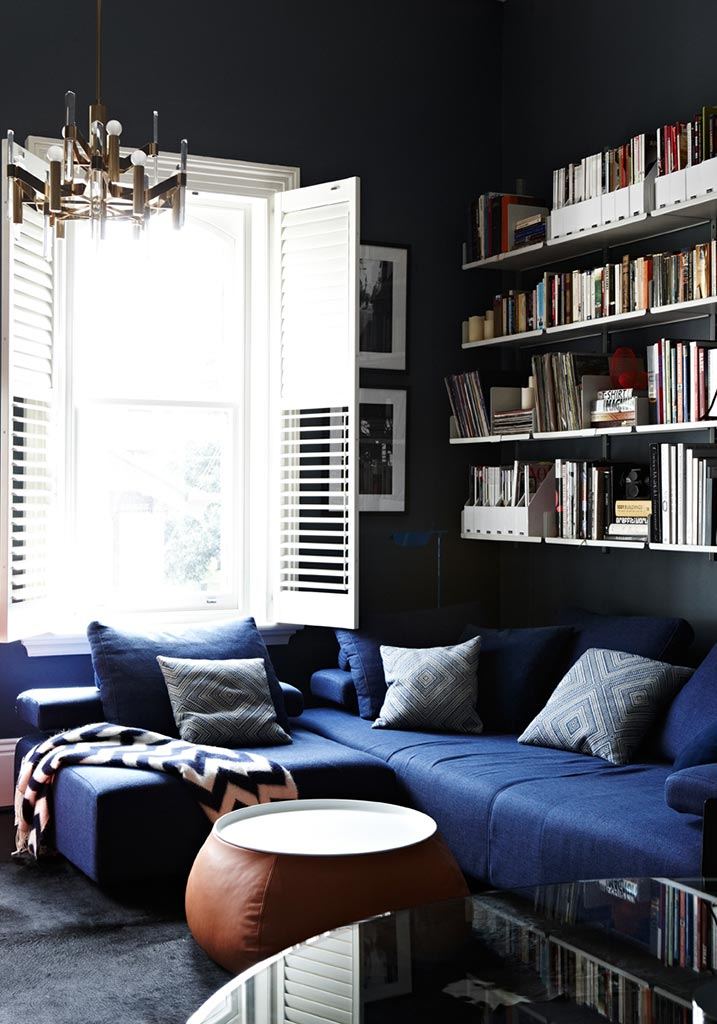 Black walls living room and blue sofa