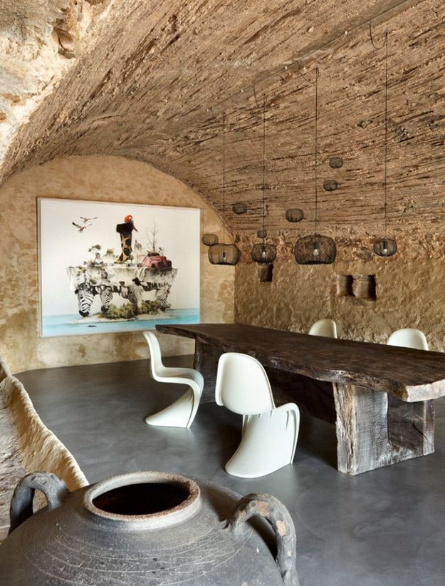 Cave castle dining room with reclaimed wood table and pantone chairs