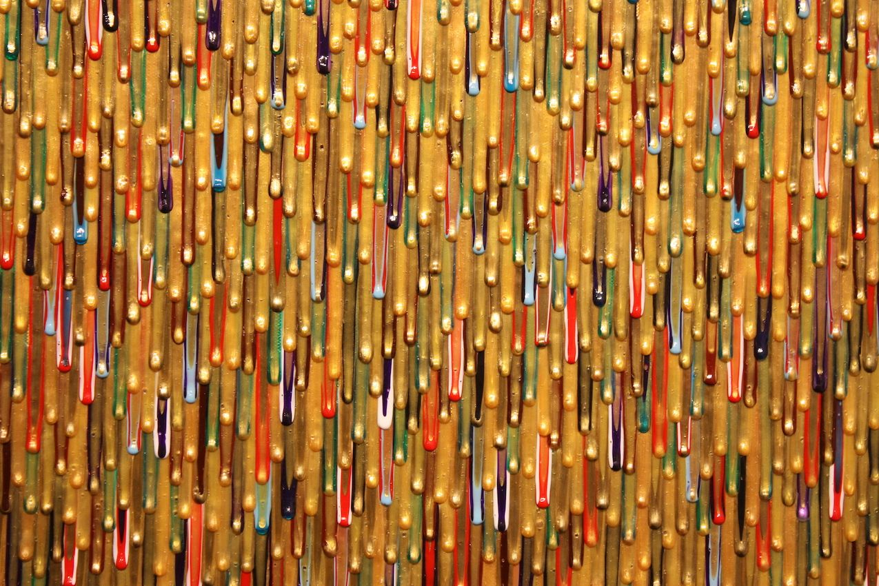 Meticulously placed drips of gold paint meld with colors to create dimension and depth.