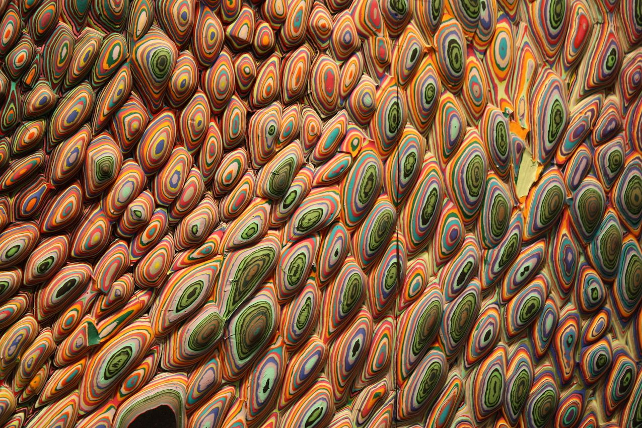 These close-ups show the different layers of paint pours that are applied to small pieces of wood and then assembled into the massive wall piece.