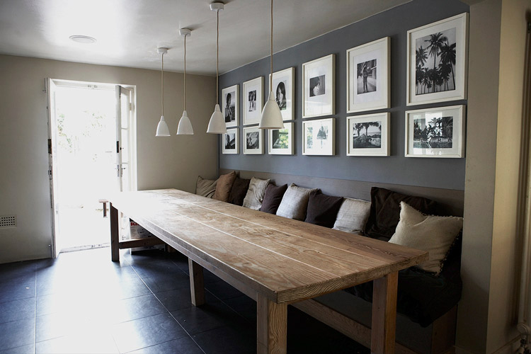 Large dining table with a built in bench and wall behind decorated with pics