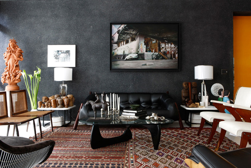 Living rom with a black wall and a mid century sofa