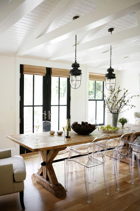 Lucite ghost chairs dining room with a farm table