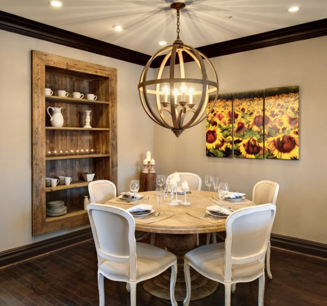 Round dining table and chandelier over it with built in shelves into the walls