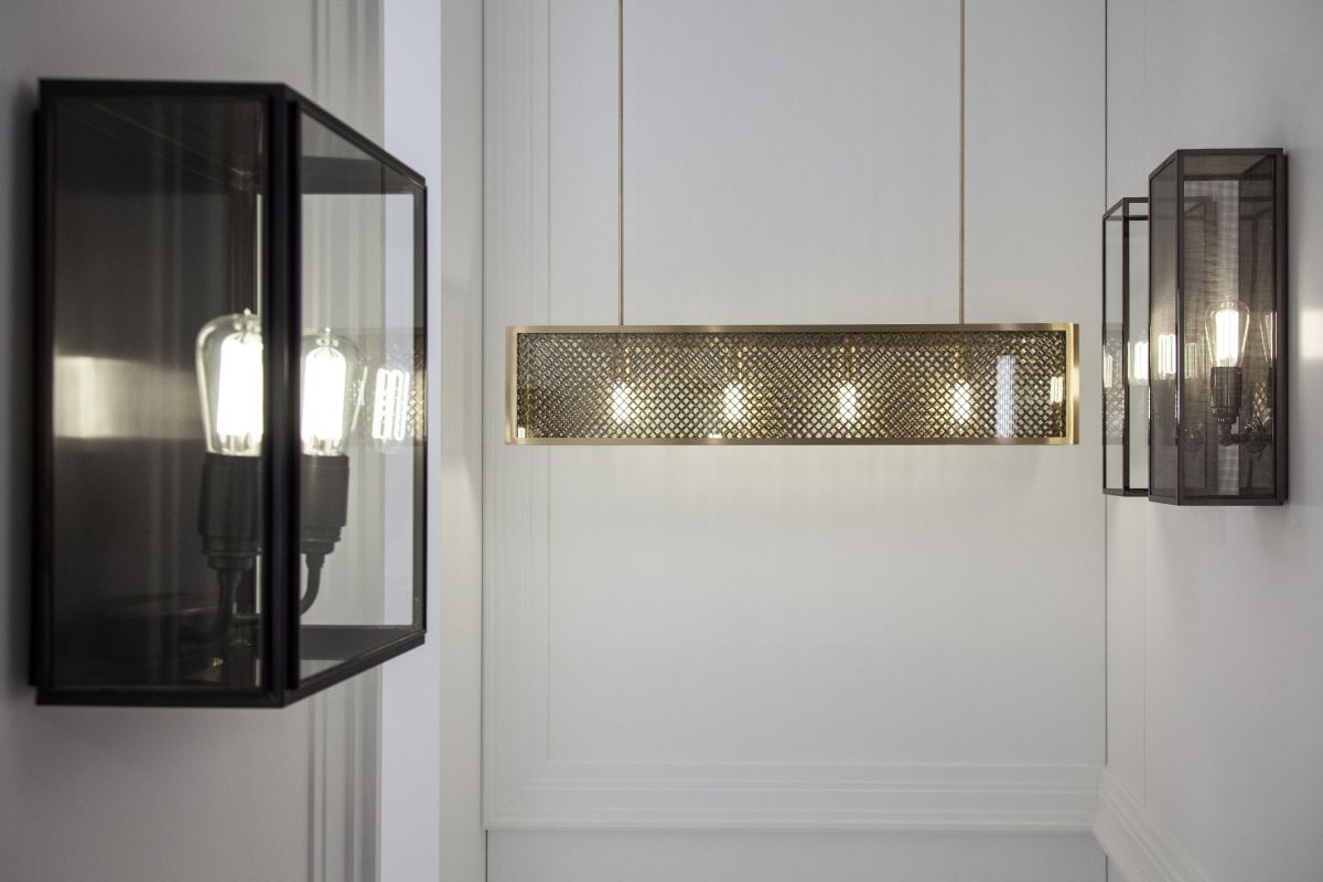 The Annet Gauze-C wall light is done in weathered brass with clear glass the fixture has a spring closure. In the background hangs the Portreath Mesh-C chandelier with sateen brass and clear glass.